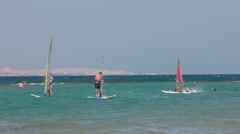 Tourists learn to slide waves with windsurfing board on windy bay of the Red Sea Stock Footage