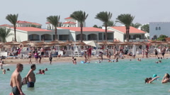 Swimming area is in the Red Sea at Hurghada resort. People are on sandy beach Stock Footage