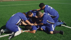 Soccer players dog pile on their teammate on the field Stock Footage