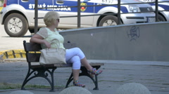 Woman sitting on a bench in a square in Warsaw Stock Footage