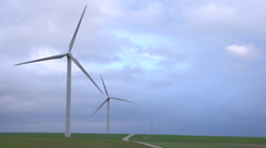 2 Windmills, wind turbines spinning in a field - nice cloudy sky background 1 Stock Footage