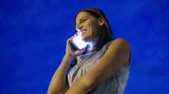 Woman chatting on cellphone at night against navy sky, steadycam shot Stock Footage