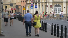 Walking, riding bikes and drivng cars on Senatorska street in Warsaw Stock Footage