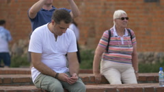 Man wearing a white shirt sitting on a small brick wall in Castle Square, Warsaw Stock Footage