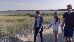 Teens Go For A Walk On Sandy Beach Path, Salt Water Pond In Background Stock Footage