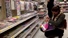 Woman choosing scrapbooks inside Walmart store. Stock Footage