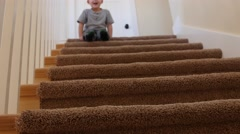 A cute little boy bouces down stairs on bum Stock Footage
