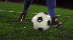 A female soccer player dribbles down the field at night while opponent tackles Stock Footage