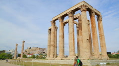 Young male and female tourists on vacation looking at majestic ancient columns Stock Footage