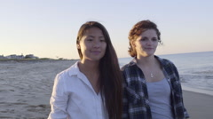 Teen Girls Walk On Beach, Their Guy Friend Sneaks Up From Behind And Hugs Them Stock Footage
