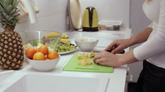 Closeup of woman hands slicing lime tangerine Stock Footage