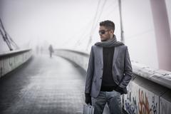 Handsome trendy man walking on a bridge in winter Stock Photos