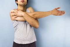 Young mixed race man stretching his arm - stock photo