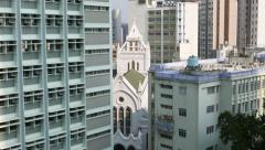 Catholic Cathedral building squeezed between tall city houses, fast burn area - stock footage