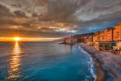 Italy, Liguria, Genoa, Camogli, Waterfront with dramatic sky at sunset Stock Photos