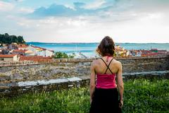 Young woman looking at the sea and her small village from a hilltop Stock Photos