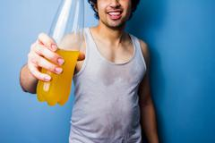 Young man drinking energy drink after a sweaty workout - stock photo
