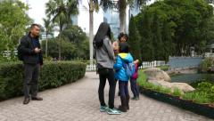 Walk along Hong Kong Park path, fine gardening area, pass Asian family Stock Footage