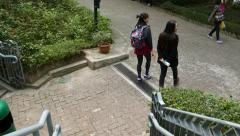 Follow two young girls climb down park staircase, come to main road Stock Footage