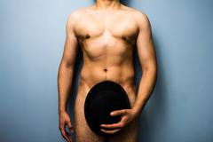 Naked man hiding his modesty with a bowler hat - stock photo