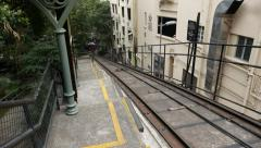 Peak tram move uphill, approach and stop at middle station, look downward Stock Footage