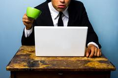 Businessman is surprised and nearly spills coffee on notebook - stock photo