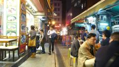 Crowded night alley full people at cheap eatery, outdoor kitchens Stock Footage