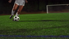 A female soccer player dribbles down the field during a game at night Stock Footage