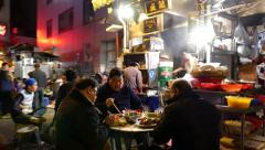 Authentic outdoor eatery on dark urban alley, people seat and eat supper Stock Footage