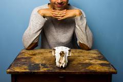 Smirking man with skull at desk Stock Photos