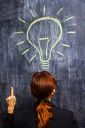 Redhead businesswoman having a bright idea - stock photo
