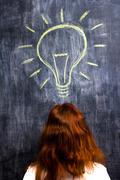 Redhead woman having a bright idea - stock photo