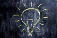 Stock Photo of Chalk drawing of lightbulb on blackboard