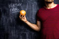 Man promoting healthy eating in front of blackboard - stock photo