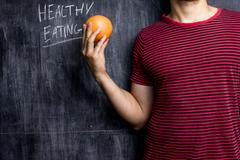 Stock Photo of Man promoting healthy eating in front of blackboard