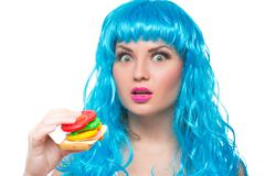 young girl doll with blue hair. plastic eating a sandwich. hunger - stock photo