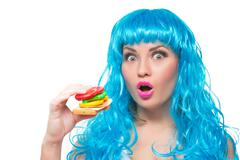 Young girl doll with blue hair. plastic eating a sandwich. hunger Stock Photos