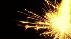 Man lights up sparkler fireworks burning on a black background Stock Footage