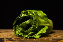Cos lettuce on wooden table - stock photo