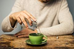 Man adding alcohol to his coffee - stock photo