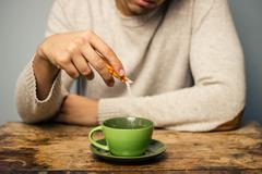 Man adding sugar to his coffee or tea - stock photo