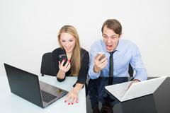 man and woman in the office for notebooks. screaming to phone - stock photo