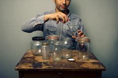 Stock Photo of Man is preparing his jars for homecooked preserve