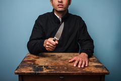 Criminal at table waving a knife - stock photo
