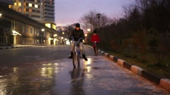 Boy rides bicycle, girl on kick scooter at surface of frozen puddle Stock Footage