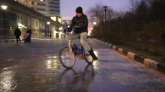 Boy rides bicycle on surface of frozen puddle and falls down. Stock Footage