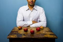 Man with five apples arranged in arrow Stock Photos