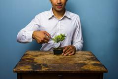 Happy man pruning his bonsai tree - stock photo