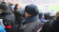 Group of policemen at Dinamo fans grandstand with raised banners Stock Footage