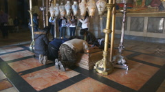 Pilgrims pray on the Stone of Anointing, Church of the Resurrection, Jerusalem - stock footage